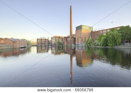 Landscape of an old brick factory and lake reflection at dusk in Tampere, Finland.