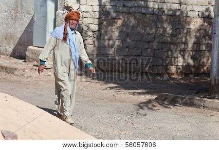 DAHAB, EGYPT - FEBRUARY 2, 2011: Man in traditional dresses walking on February 2, 2011 in Dahab, Egypt. Dishdasha is an ankle-length garment, usually with long sleeves, similar to a robe.
