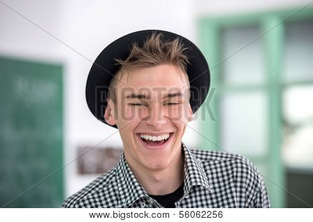 Laughing highschool boy with hat in schoolroom portrait
