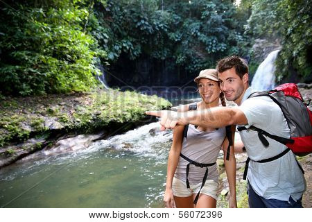 Trekkers reaching waterfall in natural landscape