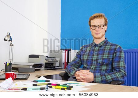 Designer, sitting back at his desk during the industrial design process of making sketches for ideation of new ideas, with his hands folded