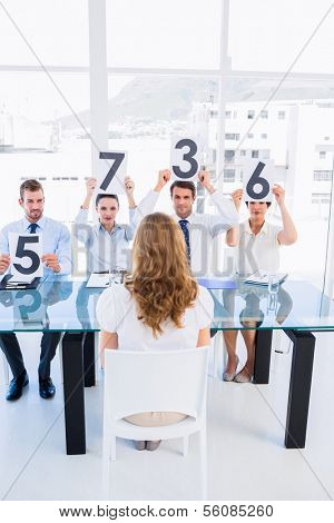 Group of panel judges holding score signs in front of a woman at bright office