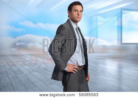 Serious businessman with hand on hip against room with holographic cloud