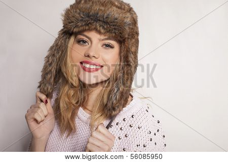 Beautiful happy young woman in a furry winter hat holding the ear flaps and smiling charmingly at the camera with copyspace behind her as she stands sideways to the camera
