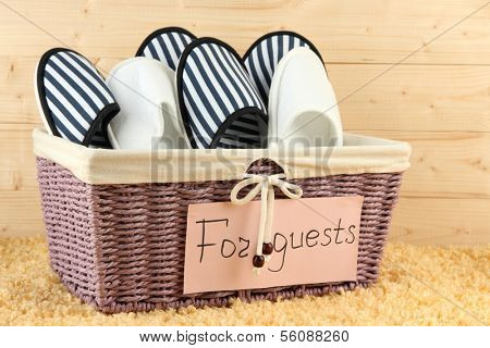 Slippers in basket on carpet on wooden background