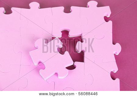 Last piece of jigsaw puzzle, close-up, on purple background