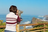 Girl Tourist Watching A Beautiful Sea Landscape From The Telescope.
