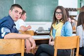 High school students sitting backwards in classroom