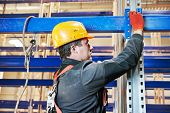 stock photo of erection  - One warehouse worker in uniform during rack erection work installation - JPG