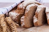 foto of fresh slice bread  - homemade fresh baked bread and knife on wooden table - JPG