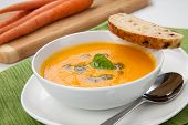 stock photo of whole-wheat  - Creamy carrot soup with basil oil garnished with herb whole wheat bread - JPG