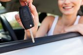picture of rental agreement  - young smiling woman sitting in car taking key handover rent purchase