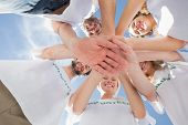 pic of morals  - Low angle view of happy volunteers with hands together against blue sky - JPG