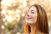 stock photo of smiling  - Portrait of a beautiful woman doing breath exercises with an autumn unfocused background - JPG