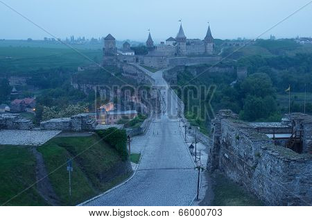Road leading to the medieval castle. Fortification historical landmark. Cityscape at dusk. Kamenetz-Podolsk, Ukraine, Europe