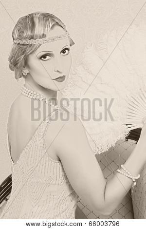 Old photo effect of a vintage twenties woman with feather fan