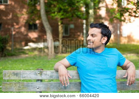 Happy man sitting on bench