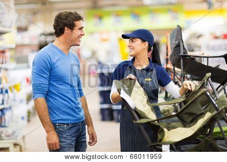 friendly saleswoman selling camping chair to customer in supermarket