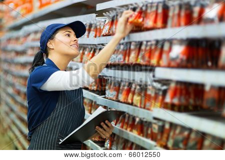 attractive hardware store worker counting stock
