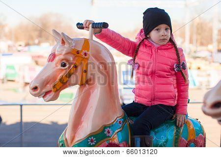 Little happy girl on carousel at an amusement park