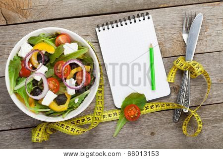 Fresh healty salad on wooden table and kitchen utensil with notepad for copy space