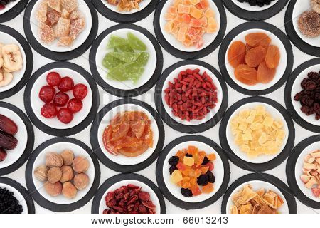 Dried fruit selection in white bowls on slate rounds over white background.