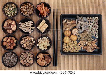 Large chinese herbal medicine selection in wooden bowls and square dish with chopsticks over bamboo.
