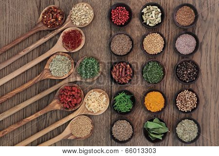 Herb and spice food seasoning selection in wooden spoons and bowls over oak wood background.