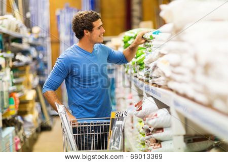 young man shopping for fertilizer in hardware store
