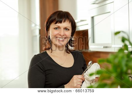 Middle-aged Woman Wipes The Dishes In The Kitchen