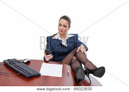 Brunette Businesswoman Sitting At Desk With Smartphone