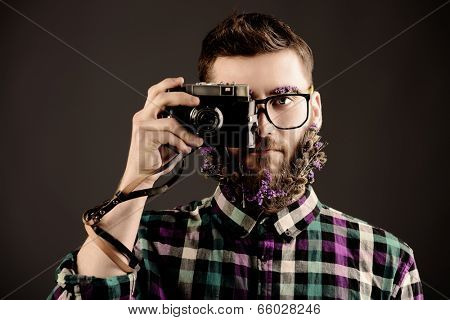 Extravagant young man with a beard of flowers making photographs.