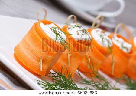 Rolls Of Fresh Carrots With Soft Cheese On The Table