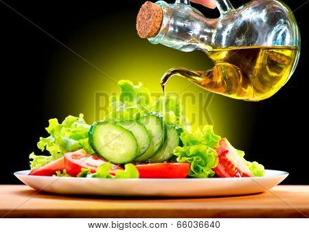 Healthy Vegetable Salad with Olive oil dressing. Pouring Olive oil. Healthy vegetarian food. Vegan. Diet, dieting concept. Lettuce, tomatoes, cucumbers. Organic bio food.