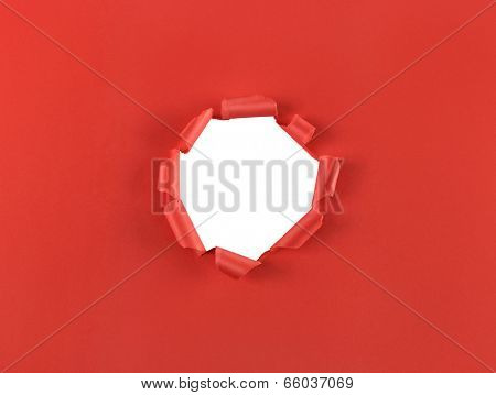 Ripped hole in red paper isolated over a white background