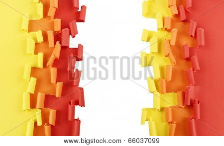 Ripped and curled paper background in orange, yellow and red, isolated over white