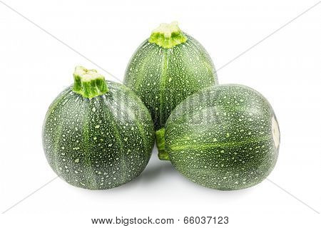 Three round zucchini on a white background