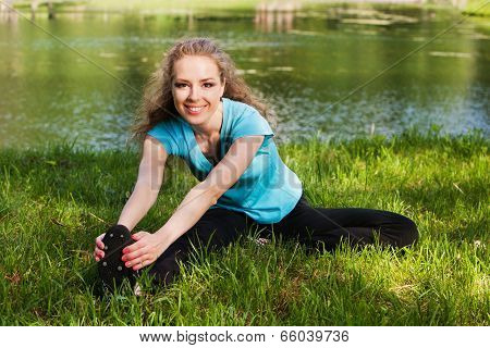 Exercise woman stretching hamstring leg muscles during outdoor running workout. Smiling happy Caucas