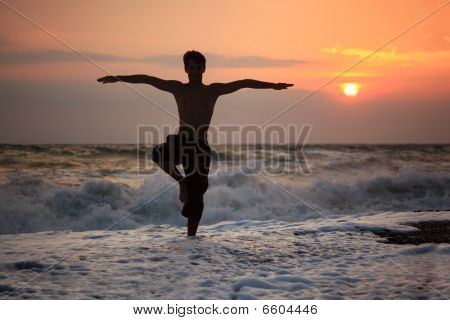 Silhouette Guy Yoga On Sunset Wavy Beach