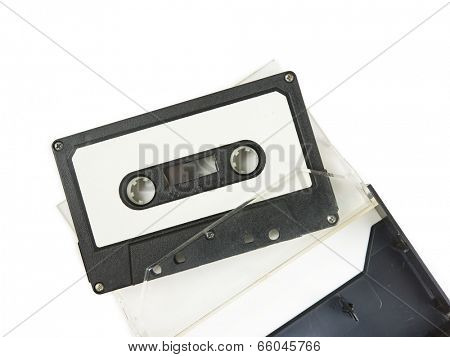 Early 70's cassette tape loosely detached from an open cassette case, on natural white background.