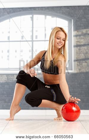 Beautiful young rhytmic gymnast practicing with ball, squatting, smiling.
