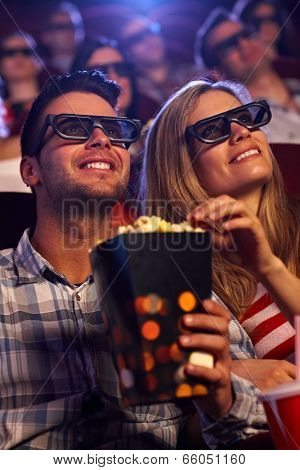 Young couple sitting in auditorium of multiplex movie theater, watching 3D movie, eating popcorn, smiling.