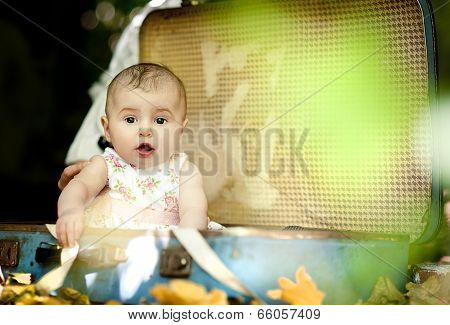 Cute baby girl in old suitcase