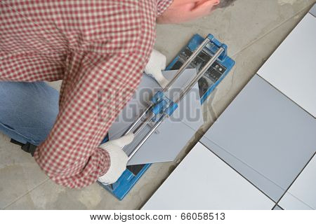 Tiler cutting ceramic tiles during floor installation