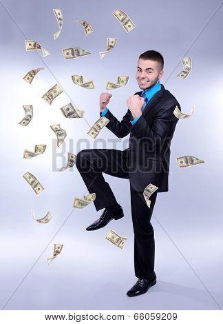 Happy man enjoying rain of money, on grey background