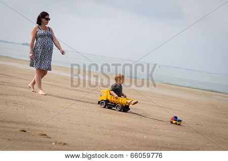 Mother Pulls Her Son On The Beach