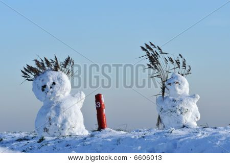 Snowmen On Dike In The Netherlands