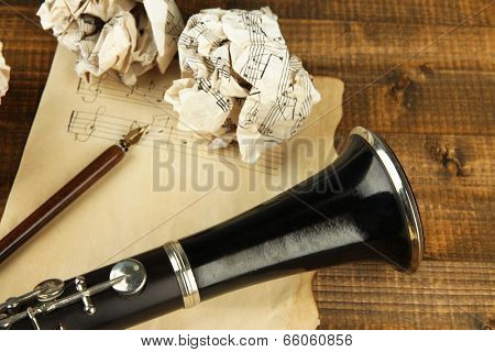 Crumpled paper balls with music sheet and clarinet on wooden background