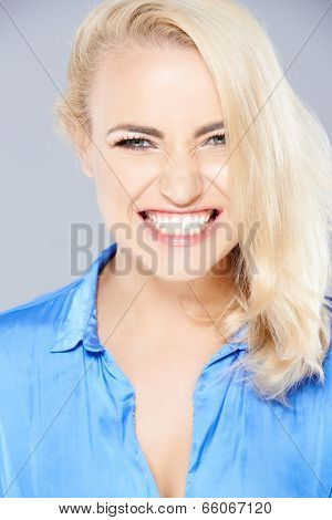 Beautiful blond woman gnashing her teeth and snarling at the camera with a fierce expression
