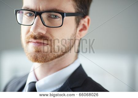Serious businessman in eyeglasses looking at camera